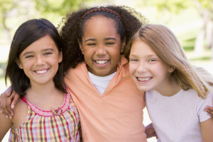 Three young girl friends outdoors smiling